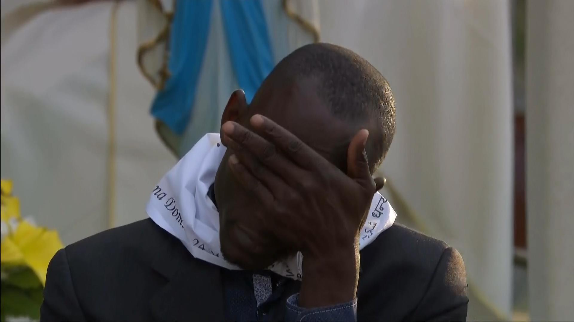 One of the refugees is overcome with emotion during the Pope's Holy Thursday Mass