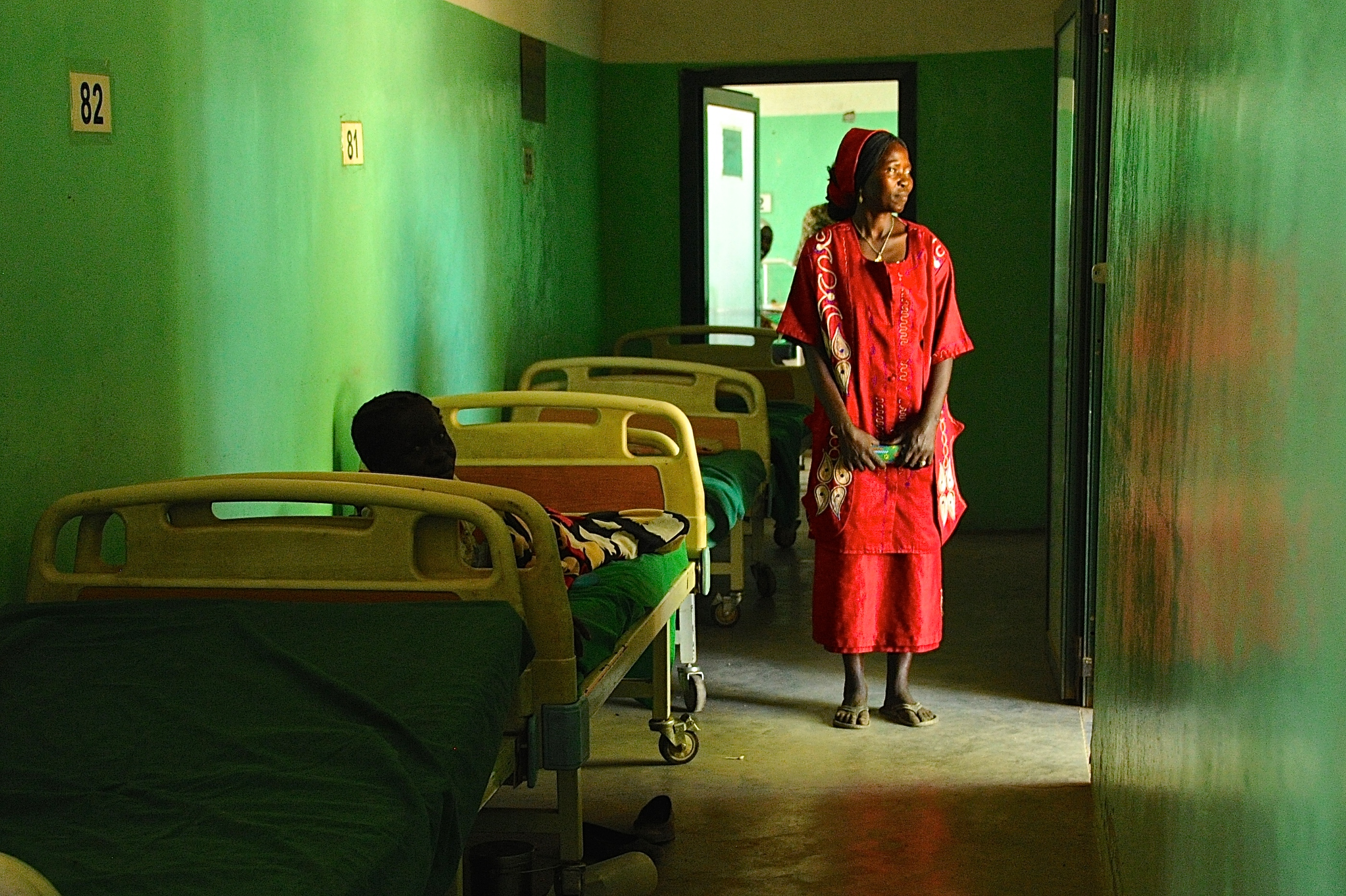 A mother stands by her child's bed at Mother of Mercy hospital
