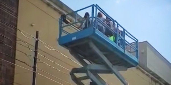 Friends use scissor lift to visit friend with cancer through the window